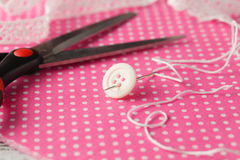 Needle and button on pink polka dot cloth Stock Images