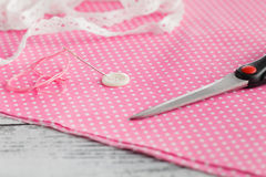 Needle anв button pinned on polka dot cloth Stock Photo