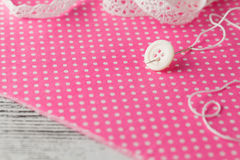 Needle anв button pinned on polka dot cloth Stock Photos