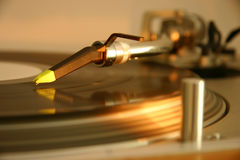 Needle and cartridge on a silver DJ turntable. Needle, cartridge and tonearm on a silver DJ turntable, with spinning platter, record and light Stock Image