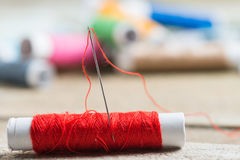 Needle and colored spools of threads Royalty Free Stock Photos