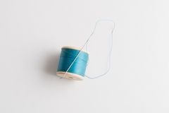 Needle Fastened on to Spool of Blue Thread Stock Photos