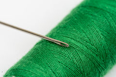 Needle head on the green thread over white background Royalty Free Stock Images