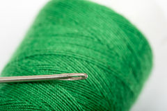 Needle head on the green thread over white background Stock Image