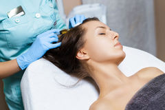 Needle mesotherapy. Cosmetic been injected in woman`s head. Thrust to strengthen hair and their growth. Needle mesotherapy. Cosmetic been injected in woman`s Royalty Free Stock Images