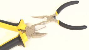 Needle-nose pliers and mini cutters on white stock footage