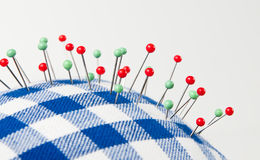 Needle in pin cushion. Red and green needles in pin cushion royalty free stock image