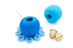 Needle, plastic buttons, thimbles and thread Royalty Free Stock Images