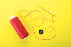 Needle with the red thread and clothing button. Spool of red thread, needle and clothing button on yellow background,  symbol of handmade and needlework Royalty Free Stock Photos