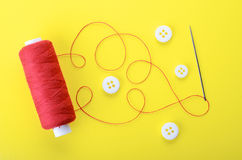 Needle with the red thread and clothing buttons. Spool of red thread, needle and clothing buttons on yellow background,  symbol of handmade and needlework Stock Photos