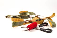 Needle with red thread, old tailors measurment tape and scissors stock photos