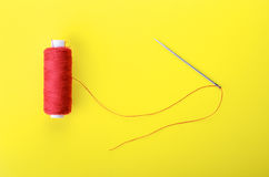 Needle with the red thread. Spool of red thread and needle on yellow background,  symbol of handmade and needlework Stock Photo