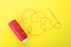 Needle with the red thread. Spool of red thread and needle on yellow background,  symbol of handmade and needlework. Copyspace Royalty Free Stock Photos