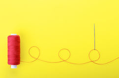 Needle with the red thread. Spool of red thread and needle on yellow background,  symbol of handmade and needlework. Copyspace Royalty Free Stock Photo