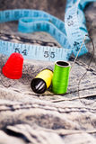 Needle, reels of cotton and a tape on denim cloth. Needle, two colourful reels of cotton, a thimble and a tape measure on denim cloth for sewing, alterations or Stock Image