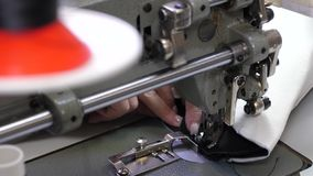 Needle of the sewing machine quickly moves up and down. process of sewing leather goods. Tailor sews black leather in. A sewing workshop. needle of the sewing royalty free stock photography