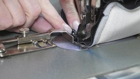 Needle of the sewing machine quickly moves up and down. process of sewing leather goods. Tailor sews black leather in. A sewing workshop. needle of the sewing stock images