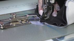 Needle of the sewing machine quickly moves up and down. process of sewing leather goods. Tailor sews black leather in. A sewing workshop. needle of the sewing stock photos