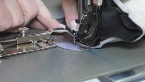 Needle of the sewing machine quickly moves up and down. process of sewing leather goods. Tailor sews black leather in. A sewing workshop. needle of the sewing royalty free stock photo