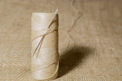 Needle. Skein of thread with a needle on a burlap background Stock Photography