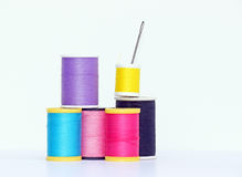 Needle and Spools of Thread. Colorful spools of thread and a needle on white background royalty free stock photos