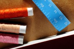 Needle, spools with threads, book and a tape measure. Bright Set Needle, spools with color threads, book and blue tape measure with inches and centimeters on Stock Photos