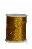 Needle stuck in spool gold thread isolated on white background. The needle stuck in a spool of gold thread isolated on white background royalty free stock photos