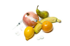 Needle and syringe injected in the fruit. Healthy life versus unhealthy life. Fruits and pills on the table. Royalty Free Stock Photos
