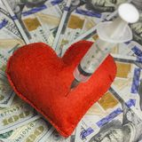 Shallow depth of field. The needle of the syringe is stuck in a red homemade heart made of cloth on a background of dollars. The c. The needle of the syringe is Stock Photo