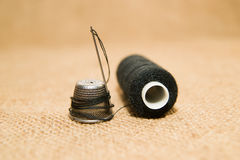 Needle, thimble and thread spool on the old cloth Stock Photos