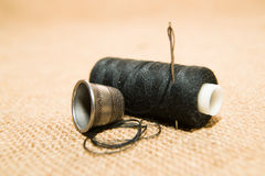 Needle, thimble and thread spool on the old cloth Stock Photography