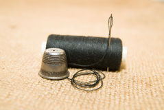 Needle, thimble and thread spool on the old cloth Royalty Free Stock Photos