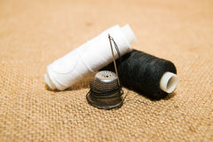 Needle, thimble and thread spool on the old cloth Royalty Free Stock Photo