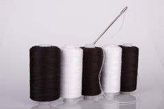Needle and thread. Reels of black and white cotton with needle royalty free stock image
