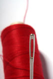 Needle and thread. Sewing supplies with a red thread in the background Stock Image