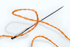 Needle and thread. Needle and orange thread over white Royalty Free Stock Photos