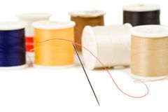 Needle and Thread. Sewing needle threaded with red, various colored spools in background Stock Images