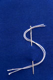 Needle and thread in dollar sign shape. On blue fabric, closeup shot Royalty Free Stock Photo