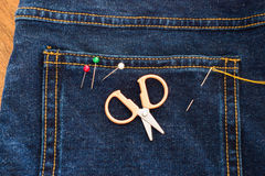 Needle with a thread through the jean Royalty Free Stock Photo