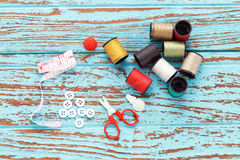 Needle thread sewing tailor thimble buttons scissors repair. Background blue wood teak still life vintage color stock photography