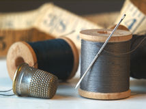 Needle, Thread, and Thimble. Wooden spools of thread with a needle and thimble Stock Photography