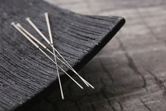 Needles for acupuncture and special stand. On grey background, closeup stock photography