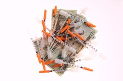 Needles and dollars. Group of needles sitting on dollars as a concept of the cost of drugs or illicit drug trade Royalty Free Stock Photography
