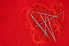 Needles and red thread. On red fiber canvas Royalty Free Stock Photography
