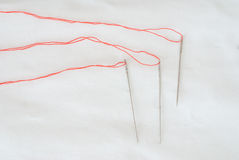 Needles with red threads. Three needles with red threads on white fabric background Stock Photography