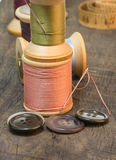 Needles and sewing thread with buttons. Needles and sewing thread on spools with buttons Stock Photos