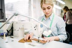 Needlewoman шьет ткани на швейной машине стоковое изображение