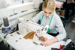 Needlewoman sews fabrics on a sewing machine. Tailoring or dressmaking on clothing factory, needlework, seamstress in workshop Stock Image