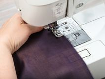 Needlewoman sews strips of fabrics for patchwork. Workshop on sewing a patchwork scarf - needlewoman sews strips of fabrics for the future silk shawl with sewing Stock Photography