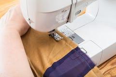 Needlewoman stitches the silk patchwork scarf. Workshop on sewing a patchwork scarf - needlewoman stitches the silk shawl with sewing machine Stock Photos